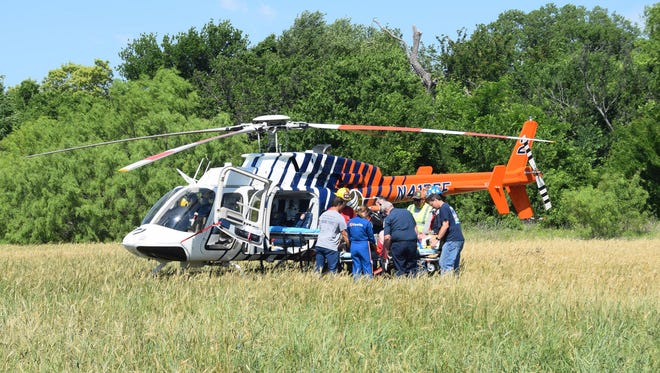 Medical personnel load a man into a helicopter after he was reportedly involved in a crash near Bowie Saturday morning.