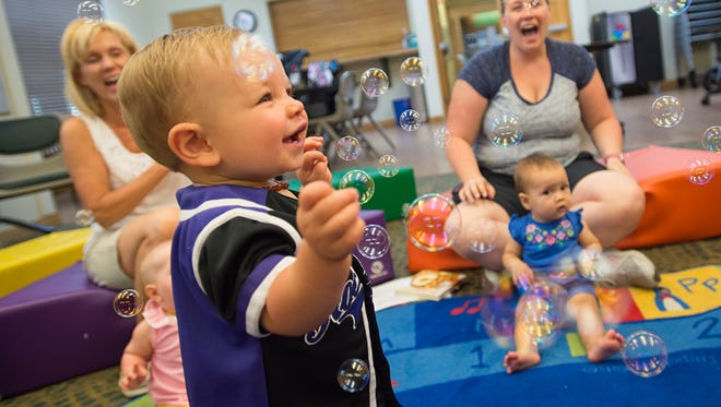 Henry Ashley, 1, dances as bubbles fly during a children's program at the Windsor Severance Library Friday in Windsor. Clearview Library District, which operates the library, is seeking to build a larger, $20 million facility on Main Street.
