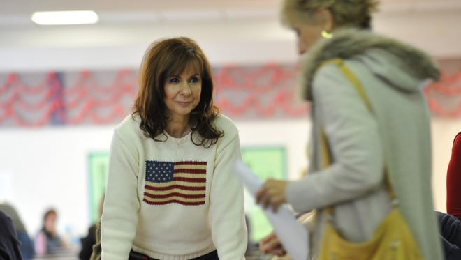A woman checks in voters during a Republican caucus at Becker Middle School February 4, 2012 in Las Vegas.
