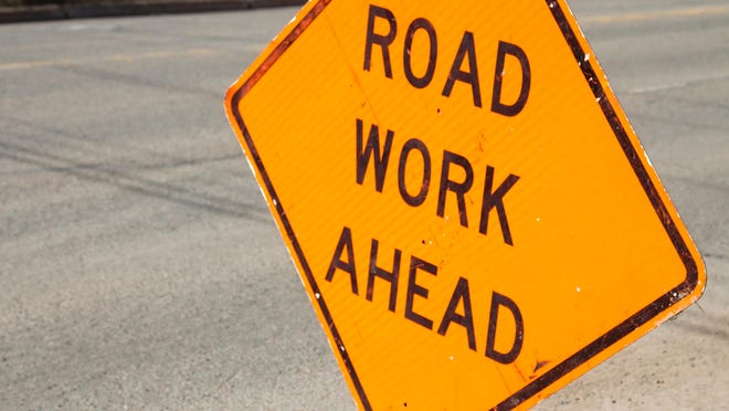 Image of an orange, diamond shaped Road Work Ahead sign on the side of an asphalt road. The road is empty. The caution sign is to warn drivers of road construction or maintenance.
