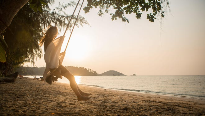 Young woman enjoying her holidays on a swing by sunset time on a tropical Island.