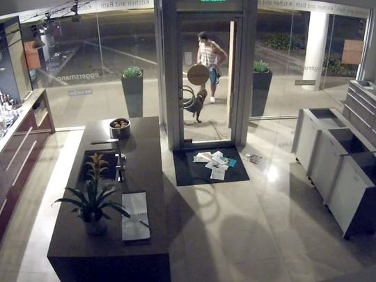 This video image shows a man with a dog after the man urinated through a mail slot at a Scottsdale business, police say.