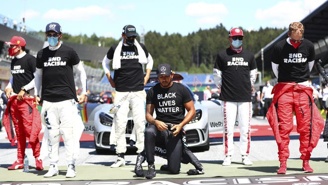 Mercedes driver Lewis Hamilton of Britain, center, takes a knee in support of the Black Lives Matter movement before the Austrian Formula One Grand Prix race at the Red Bull Ring racetrack in Spielberg, Austria, on Sunday. (DAN ISTITENE/POOL VIA AP]