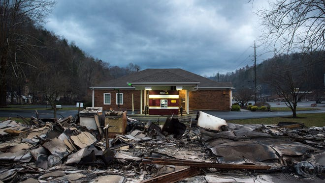 The remains of Creek Place Efficiencies in front of an unharmed BB&T bank in Gatlinburg, Tenn., Wednesday, Nov. 30, 2016. Tornadoes that dropped out of the night sky killed several people in two states and injured at least a dozen more early Wednesday, adding to a seemingly biblical onslaught of drought, flood and fire plaguing the South.  (Andrew Nelles/The Tennessean)