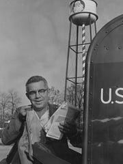 Santa Claus, Indiana postmaster Elbert Reinke lifts one of the dozen bags of mail which come daily to the Santa Claus Post Office. Dec. 28, 1970