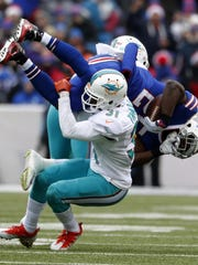 Miami Dolphins free safety Michael Thomas (31) takes down Buffalo Bills running back LeSean McCoy (25) in the first quarter of an NFL football game in Orchard Park, N.Y., Saturday, Dec. 24, 2016. (Al Diaz/Miami Herald via AP)