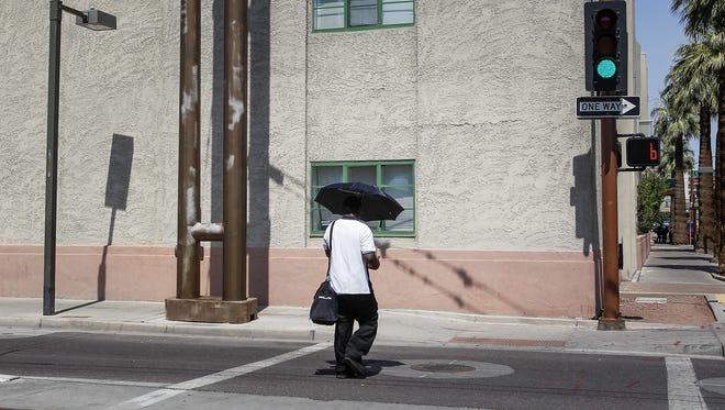 Vince Taylor from Phoenix shades himself with an umbrella on the corner of First Avenue and Fillmore Street on June 20, 2016.