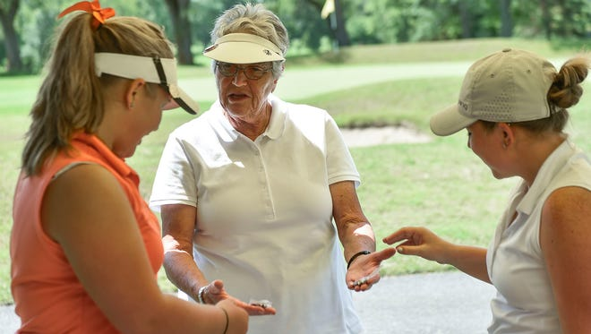 Andy Fischer, the founder of the Ohio Girls Junior Championship and a retired LPGA touring pro, gives commemorative pins to participants of this year's tournament at the Marion Country Club on Monday morning. Fischer was the first player on the LPGA Tour to use a Ping putter in 1962.