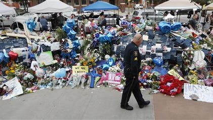 A policeman visits a makeshift memorial at the Dallas police headquarters, Monday, July 11, 2016, in Dallas. Five police officers were killed and several injured during a shooting in downtown Dallas last Thursday night.