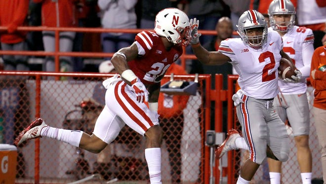 Ohio State tailback J.K. Dobbins throws a stiff-arm at the Nebraska 25 en route to completing a 52-yard touchdown run.