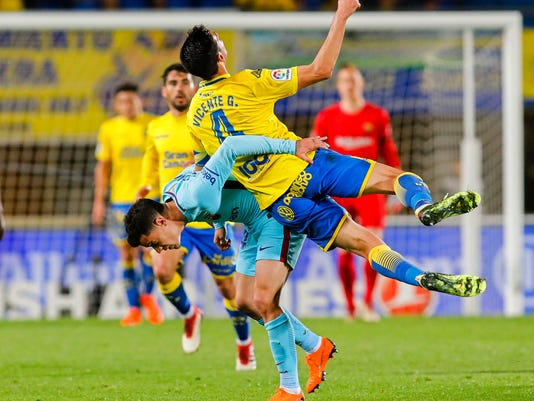 FC Barcelona's Philippe Coutinho, left, duels for the ball with Las Palmas' Jose Vicente Gomez during a Spanish La liga soccer match at the Gran Canaria stadium in the Canary island of Las Palmas, Thursday March 1, 2018. (AP Photo/Lucas de Leon)