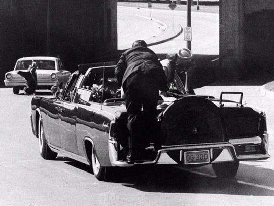 President John F. Kennedy slumps down in the back seat