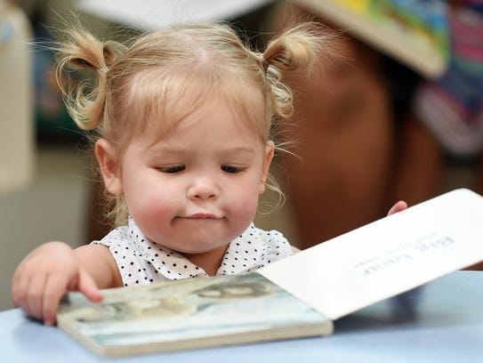 In this 2014 file photo, a young girl looks at a book
