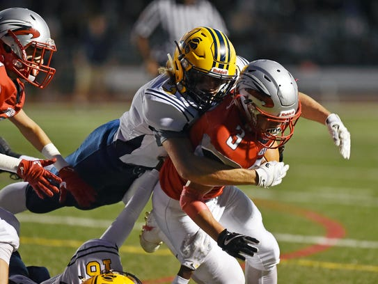 Dover's Derek Arevalo gets tackled by Eastern York's