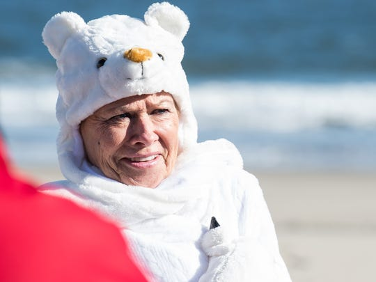 A woman awaits the start of the 24th Annual Penguin Swim in costume near the Princess Royale Hotel in Ocean City on Monday, Jan. 1, 2018.