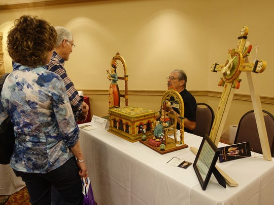 Patrons visit the booth of Federico Prudencio at the Las Cruces Spanish Market in 2016.
