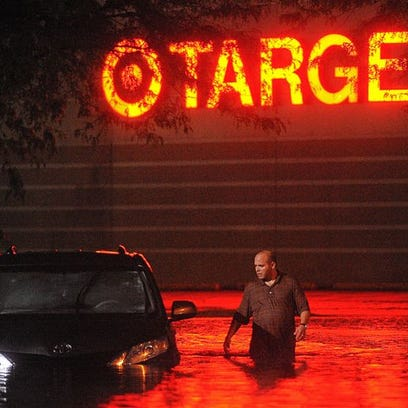 A man looks into a flooded car while wading through