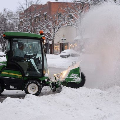 A plow clears snow from an Old Town Fort Collins street
