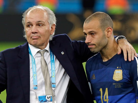 Argentina's head coach Alejandro Sabella stands with Javier Mascherano (14) after the World Cup final soccer match between Germany and Argentina at the Maracana Stadium in Rio de Janeiro, Brazil, Sunday, July 13, 2014. Germany won the match 1-0. (AP Photo/Matthias Schrader)