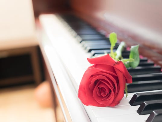 Piano with red rose flower in church. vintage filter effect.