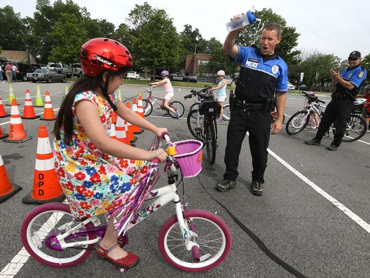 Denville Police Ptl. Bill Underwood celebrates with 8-year-old Carolina Contreras of Denville after she made it through the course for the first time during the 3rd Annual Denville Kiwanis Bicycle Rodeo with the Denville Police Department.  June 8, 2017, Denville, NJ.