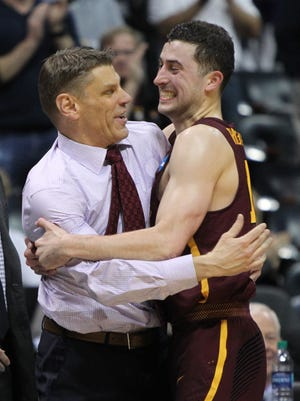 Loyola Ramblers guard Ben Richardson (14) hugs Loyola Ramblers head coach Porter Moser at the end of the championship game of the South regional of the 2018 NCAA Tournament at Philips Arena.