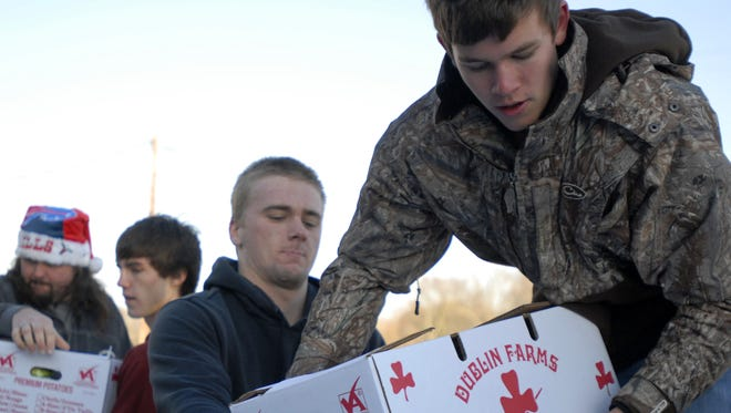 Broadwater Academy students Preston Richardson, second from right, and Will Sexauer load a food package onto a truck Wednesday, Dec. 18, 2013 at the Foodbank in Tasley. Students and community volunteers delivered 200 packages for the Eastern Shore News' 53rd annual Bank of Cheer.