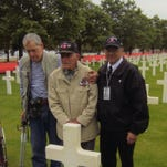 Gene Garren, left, Ray Fary and Rick Holle visit Paul Snyder's grave near Omaha Beach on their trip last year.