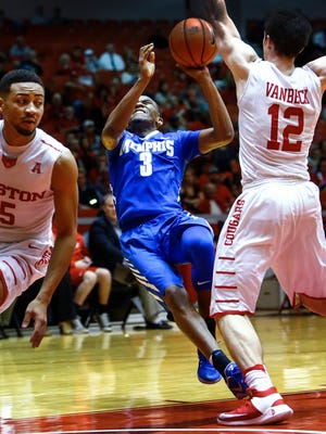 University of Memphis guard Jeremiah Martin (middle) is fouled on a fast break while defended by University of Houston teammates Galen Robinson Jr. (left) and Wes VanBeck (right) during first half action at the Hofhienz Pavilion in Houston, Texas.