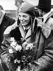 American aviatrix Amelia Earhart poses with flowers