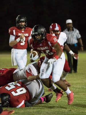 West Florida High running back, Devin Abrams, (No. 16) powers his way through the Pine Forest High defense during Friday night's game.