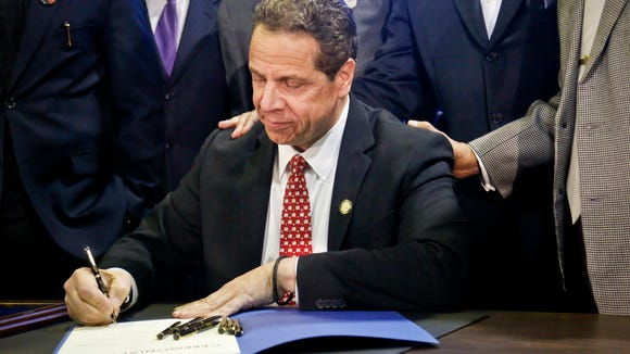 New York Gov. Andrew Cuomo signs new legislation for free state college tuition and juvenile justice reform, Monday April 10, 2017, during a signing ceremony in New York. (AP Photo/Bebeto Matthews)
