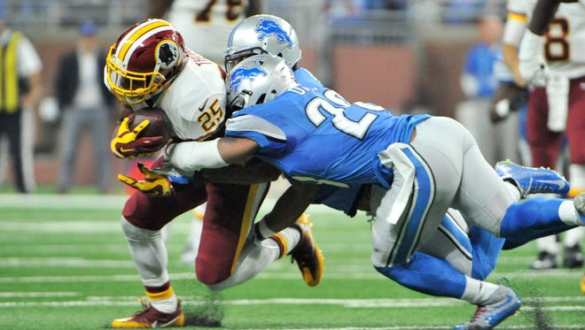 The Lions' Glover Quin and Quandre Diggs bring down Washington running back Chris Thompson in the second quarter.