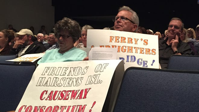 Residents came armed with protest signs during a public hearing regarding a proposed Harsens Island bridge on Wednesday, March 9, 2016.