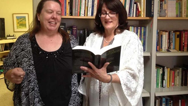 Jeannie Kay, left, and the Rev.Carla Friedrich look over a volume in the library of the New Church of the Southwest Desert on Sunday.
