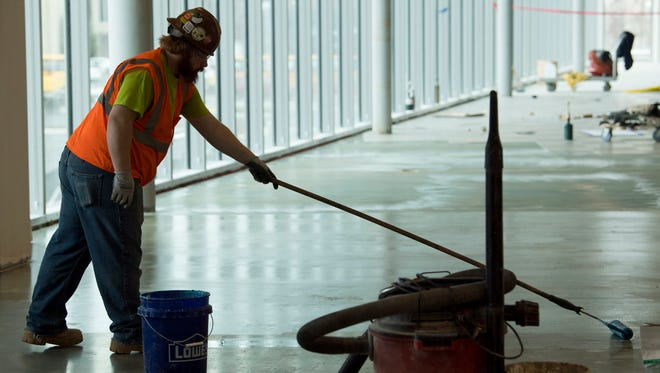Christian Johnson with Rasure Flooring applies a moisture barrier on the second floor of the Indiana University School of Medicine-Evansville Thursday morning.