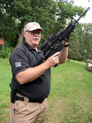 Curt La Haise is a shooting instructor, former police officer and a National Rifle Association member, seen here at his shooting range in Deerfield. La Haise is the owner of Guardian Safety & Security Solutions, which provides self-defense training. He holds a semi-automatic AR-15 rifle.