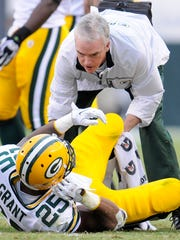 Green Bay Packers running back Ryan Grant (25) is assisted by Packers head athletic trainer Pepper Burruss after Grant was injured in a 2010 game against the Philadelphia Eagles at Lincoln Financial Field in Philadelphia.