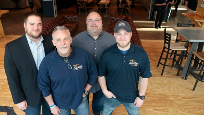 Co-founders Jake Rouse, from left, Richard Dube, Greg Rouse and Evan Rouse stand in the new Braxton Brewing Company Taproom, which opens Friday, March 27 on W. Seventh St. in Covington.