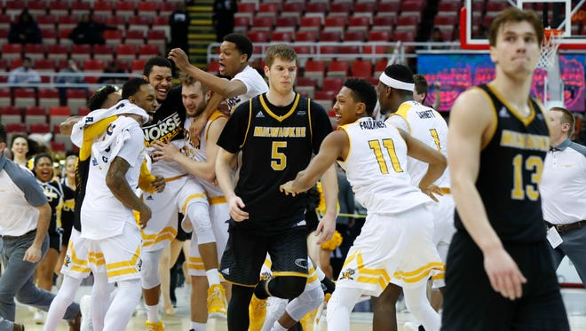 UW-Milwaukee's Cody Wichmann (center)  and August Haas walk off the floor as Northern Kentucky players celebrate a victory in the Horizon title game on Tuesday night.