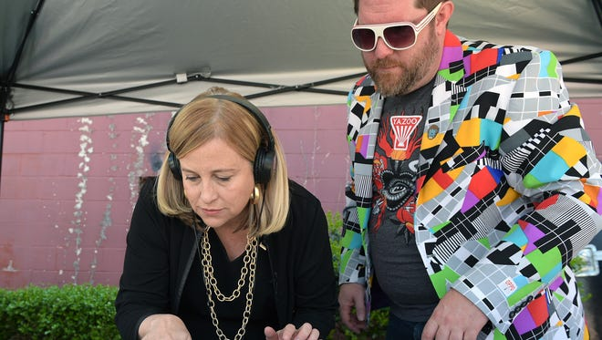 Mayor Megan Barry, left, spins records with the help of DJ Pimpdaddysupreme at Grimey's during Record Store Day April 16, 2016.