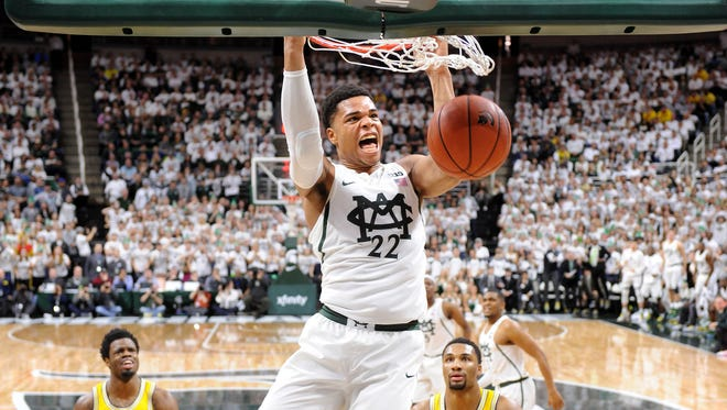 Wolverines Zack Irvin and Derrick Walton, Jr. can do nothing to stop Spartan freshman Miles Bridges on a huge dunk in the first half as MSU beats UM, 70-62 at Breslin Center Sunday afternoon, January 29, 2017 in East Lansing. (Dale G. Young/The Detroit News)