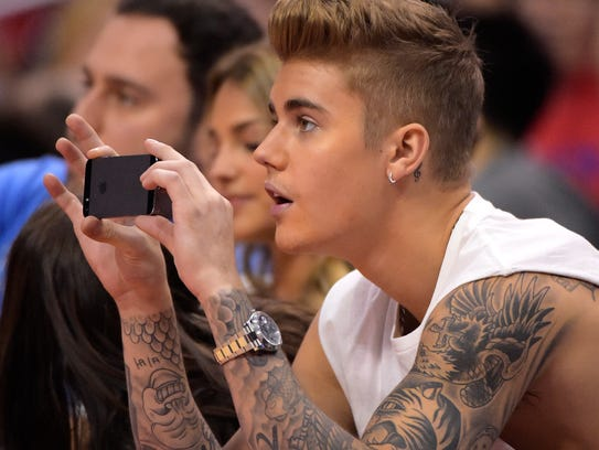 Singer Justin Bieber takes pictures  as he watches the Los Angeles Clippers play the Oklahoma City Thunder in the first half of Game 4 of the Western Conference semifinal NBA basketball playoff series, Sunday, May 11, 2014, in Los Angeles. (AP Photo/Mark J. Terrill)