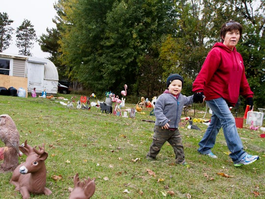 In this Sept. 30, 2014 photo, Sylus Denning walks with his babysitter Karen Maas through rows of lawn ornaments to be auctioned from Darold Mayer's yard at Mayer's family farm located southeast of Eau Claire, Wis. Mayer, 82, is in the process of selling the property and moving to Eau Claire. He will miss the farm where he and six of his seven siblings were born and where he's lived his entire life, the Leader-Telegram reported. (AP Photo/The Eau Claire Leader-Telegram, Marisa Wojcik)