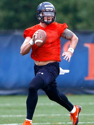 Quarterback Kurt Benkert scrambles to throw a pass during a Virginia football practice in Charlottesville on Friday, August 5, 2016.