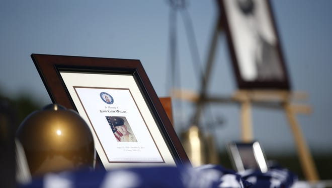 Photos and ashes are displayed at the burial of five veterans who were the first to be interred at the Tallahassee National Cemetery on Friday, Oct. 16, 2015.
