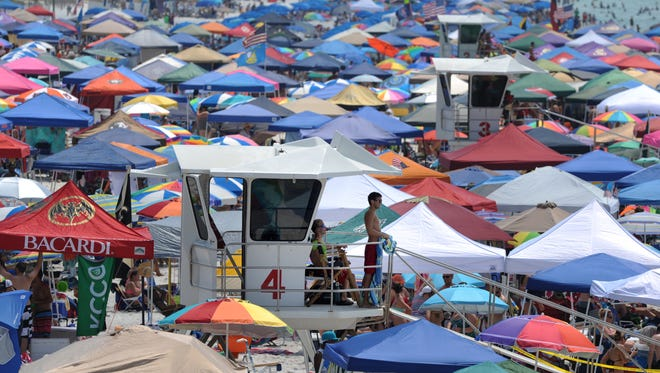 The lifeguard towers are rather hard to find amongst the tens of thousands of people, tents, and umbrellas Saturday at Casino Beach as people watch the civilian acts before the Blue Angels Air Show.