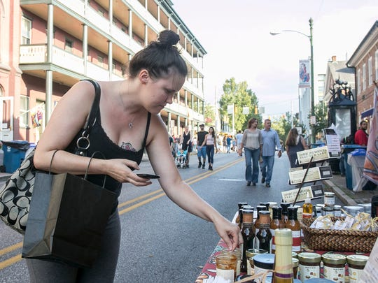 Melissa Hopkins, of Freeland, Maryland samples the chewy sesame caramel at Park Street Pantry's sidewalk sale Friday, Aug. 5, 2016. Amanda J. Cain photo