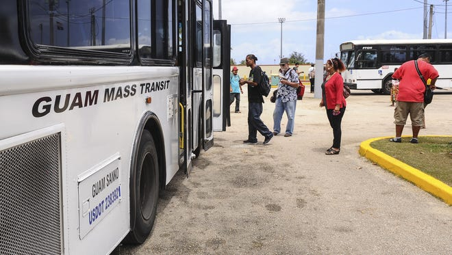 In this file photo, passengers board Guam Mass Transit Authority buses at the Paseo parking lot.