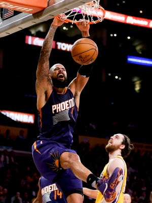 Phoenix Suns center Tyson Chandler, left, dunks over Los Angeles Lakers forward Ryan Kelly during the first half of an NBA basketball game in Los Angeles, Friday, March 18, 2016.